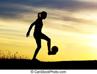 woman playing football - Silhouette of a young woman playing...