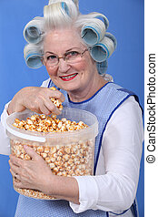 senior woman with curlers on her head eating popcorn