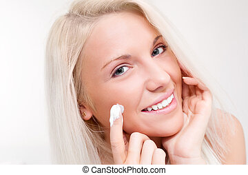 woman applying cream - beautiful young blond woman applying...