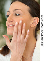 Brunette applying moisturiser