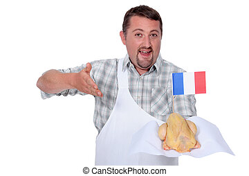 Man in a white apron offering a whole French chicken