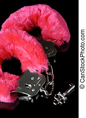Love Cuffs - Pink fluffy handcuffs with a key closeup...