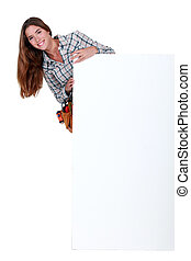 Happy female worker stood by blank advertising board