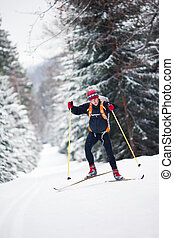Cross-country skiing: young man cross-country skiing on a...