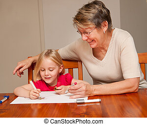 A little girl drawing with her grandmother or nanny.