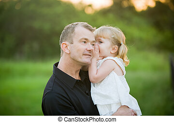 A little girl whispering a secret to her daddy - This little...
