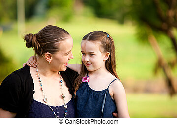 A mum with her 6 year old little girl in an outdoor field....