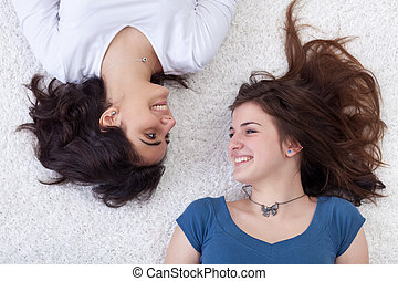 Happy girls laying on the floor