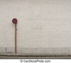 pavement and traffic sign in front of wall with white tiles