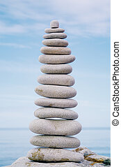 Levelling - Balancing white pebbles each other on a sky...