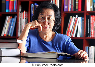 Mature Asian lady in library - Senior student reading a book...