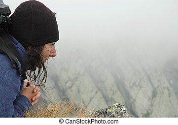 Girl sitting on the edge of summit