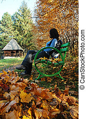 Woman on bench in park at Autumn
