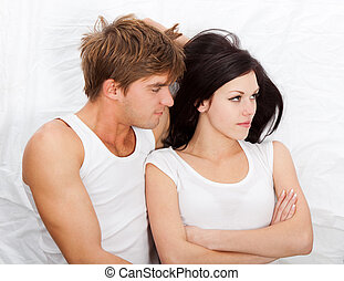 young upset couple in bed - young upset couple lying...