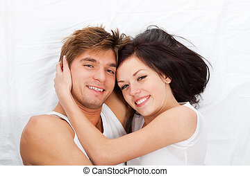 young lovely couple lying in a bed