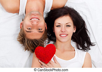 young love couple in bed holding red heart