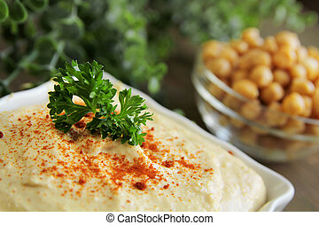 Hummus - Close up of hummus with chickpeas on a wooden table...
