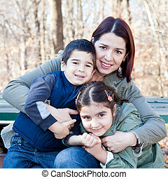 Happy Mother Hugging Her Children - Family portrait of a...