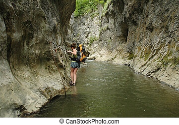Trekker in water in a gorge