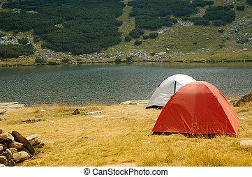 Camping tents near mountain lake - Camping tents near...