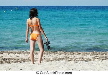 Woman in orange bikini on the beach