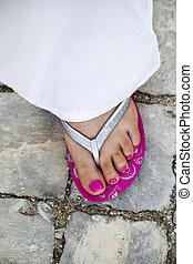 pink flip-flop footwear - Detail view of a female foot...