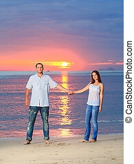 Couple - Young couple near the sea at sunrise