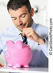Economy - businessman matting a coin in the piggy-shaped...