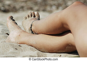Woman's sexy legs on the beach