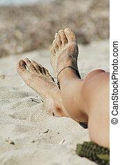 Woman's sexy legs on the beach