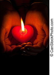 Human hands hold heart shaped burning candle against dark...