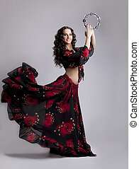 Young woman dance flamenco with tambourine - Young beauty...