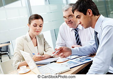 Consulting - A business team of three sitting in office and...