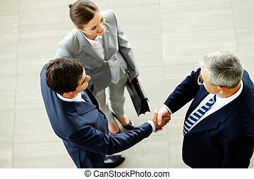Business deal - Image of business partners handshaking after...