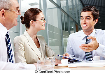 Interview - Three business partners sitting in office and...