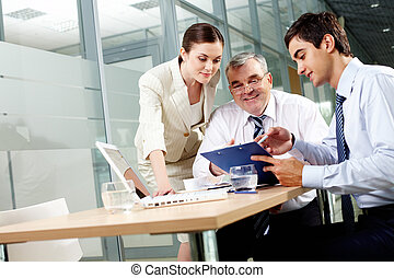 Meeting - Three business partners sitting in office and...