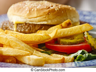 Golden French Fries with Cheeseburger in Background - Golden...