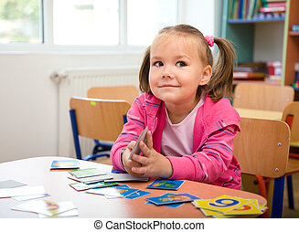 Cute little girl is playing with educational cards while...