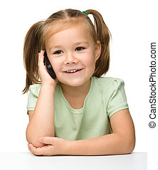Cute little girl is talking on cell phone while sitting at...