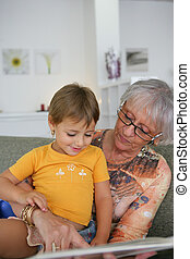 Young child reading with grandma