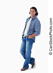 Man smiling while leaning against a wall with white...