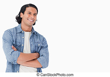 Close-up of a smiling man crossing his arms and looking...