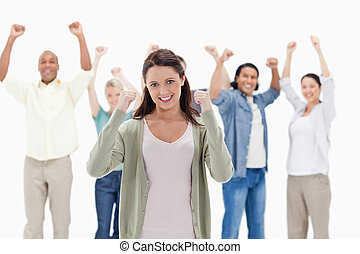 Happy people raising their arms focus on the woman in...