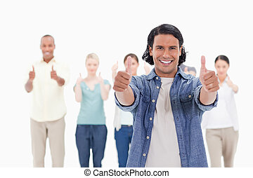 Close-up of a man smiling with his thumbs-up with people...