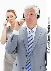 Close-up of a white hair businessman with a woman talking in background while wearing headset against white background