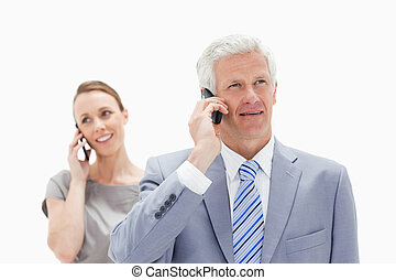 Close-up of a white man hair man dressed in a suit talking on the phone with a smiling woman in background