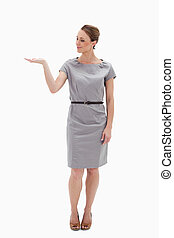 Woman in a dress presenting something with her hand against...