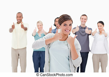 People giving the thumbs-up with a woman smiling in...