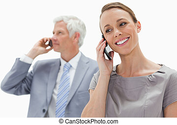 Close-up of a smiling woman making a call with a white hair businessman in background against white background