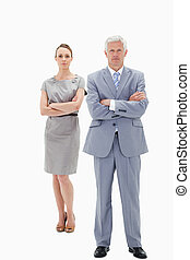 White hair businessman with a woman behind him crossing...